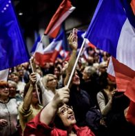 Supporters cheer and wave the French national flag as former French president and candidate for the right-wing Les Republicains (LR) party primaries ahead of the 2017 presidential election, Nicolas Sarkozy (not pictured) arrives for a campaign rally in Meyzieu on November 9, 2016. / AFP PHOTO / JEFF PACHOUD